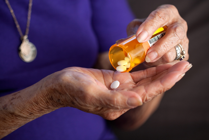 An older woman & # 39; s giving her a medicine bottle in her hand
